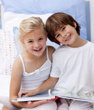 Happy brother and sister reading a book in bedroom Royalty Free Stock Photography
