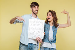 Happy brother and sister showing nameplate. Picture of happy brother and sister showing nameplate over yellow background. Looking camera Royalty Free Stock Image