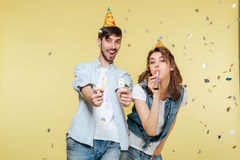 Happy brother and sister standing over yellow background. Image of happy brother and sister standing over yellow background. Looking camera royalty free stock photos