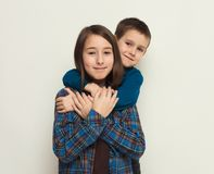 Happy brother and sister, studio background. Portrait of happy brother and sister, white studio background. Cute girl and boy posing, smiling at camera, copy Royalty Free Stock Image