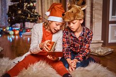 Happy brother and sister wearing Santa and deer hats sitting on a fur carpet and opens gift near a Christmas tree at stock photography