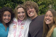 Happy brother and sisters. Handsome young man smiles with his three pretty teenage sisters stock images