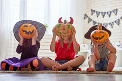 Kids at halloween. Happy brother and two sisters on Halloween. Funny kids in carnival costumes indoors. Cheerful children play with pumpkins and candy Stock Photography