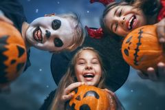 Children on Halloween. Happy brother and two sisters at Halloween. Funny kids in carnival costumes outdoors. Cheerful children and pumpkins buckets on night sky Stock Photography