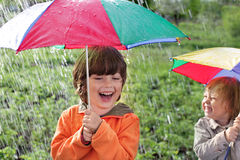 Happy brother with umbrella outdoors Royalty Free Stock Images