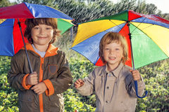 Happy brother with umbrella outdoors Royalty Free Stock Image