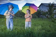 Happy brother with umbrella outdoors. Two happy brother with umbrella summer outdoors royalty free stock photography