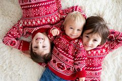 Happy brothers, baby and preschool children, hugging at home on white blanket, smiling stock photos