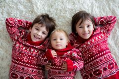 Happy brothers, baby and preschool children, hugging at home on white blanket, smiling. Shot from above stock images