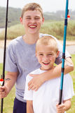 Happy brothers fishing. Portrait of happy two brothers fishing by the lake Stock Photo