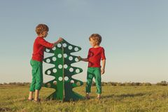 Happy brothers are playing with paper tree Stock Photos
