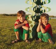 Happy brothers are playing with paper tree Royalty Free Stock Image