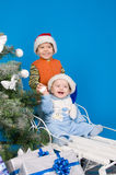 Happy brothers in Santa Claus hats. Near Christmas tree Royalty Free Stock Image