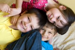 Happy brothers and sister. Two brothers and their sister snuggled up on a bed at home Stock Image