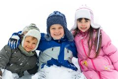 Happy Brothers And Sister In Snow. Two smiling young brothers and their sister sitting in snow, with arms around each other Stock Image