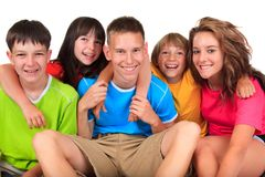 Happy brothers and sisters. Happy young brothers and sisters in colorful clothing embracing, isolated on white background royalty free stock photo
