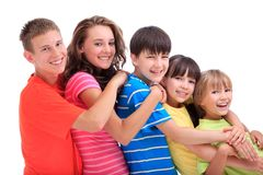 Happy brothers and sisters. Side view of five happy young brothers and sisters in ascending age and height with colourful clothes; white background stock image