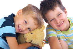 Happy brothers and teddy bear. Two happy brothers with toy bear. One is hugging it while both are smiling at the camera. White background stock photos