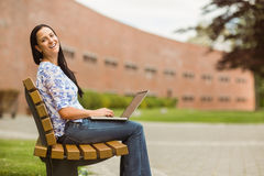 Happy brown hair sitting on bench using laptop Royalty Free Stock Photo