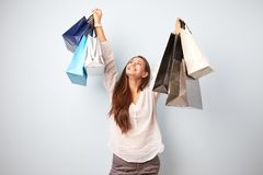 Happy brown-haired girl dressed in white blouse and gray trousers stands with lots of bags after shopping on the white stock photos
