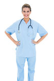 Happy brown haired nurse in blue scrubs posing with hands on the hips Royalty Free Stock Image
