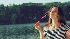 Happy brunette blowing colourful soap bubbles in summer park near pond. Slowly stock video footage