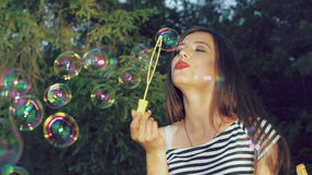 Happy brunette blowing colourful soap bubbles in summer park. Slowly stock video