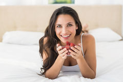 Happy brunette with bowl of strawberries Royalty Free Stock Photography
