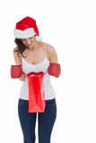 Happy brunette in boxing gloves looking in shopping bag Stock Photos