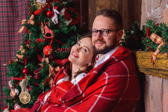 Happy brunette bride and gorgeous groom in the cozy plaid. Christmas tree. Royalty Free Stock Image