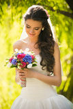 Happy brunette bride looking at wedding bouquet at park Stock Images