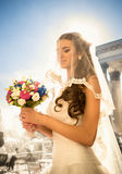 Happy brunette bride posing with wedding bouquet at sunny day Stock Image