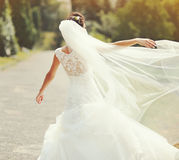 Happy brunette bride spinning around with veil Royalty Free Stock Image