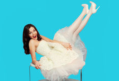 Happy brunette bride woman in white wedding dress having fun on the table over colorful blue Stock Image