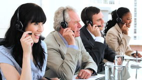 Happy brunette call centre agent working with her colleagues Royalty Free Stock Photography