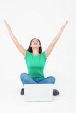 Happy brunette cheering in front of her laptop Royalty Free Stock Photos