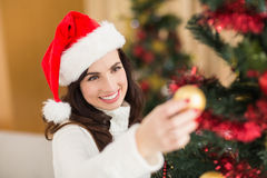 Happy brunette decorating a christmas tree Royalty Free Stock Image
