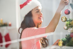 Happy brunette decorating a christmas tree Stock Photography