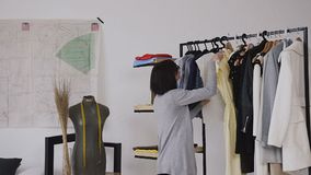 A happy brunette is doing a fitting yellow dress, which is on a hanger in the fashion designer`s studio. Clothing. Wardrobe, fashion, style and people`s stock video footage