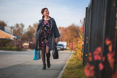Happy brunette in a dress coat and goes shopping down the street Royalty Free Stock Photos