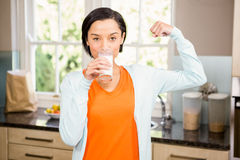 Happy brunette drinking milk and showing bicep Stock Photo