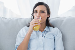Happy brunette drinking orange juice Stock Photography
