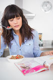 Happy brunette eating cereal and reading magazine Stock Photo