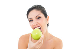 Happy brunette eating a green apple and looking at camera royalty free stock photo