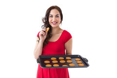 Happy brunette eating hot cookies Stock Photography