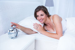 Happy brunette extending hand to alarm to clock in bed Royalty Free Stock Image