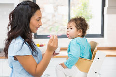 Happy brunette feeding her baby. In the kitchen Stock Photos