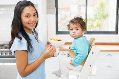 Happy brunette feeding her baby. In the kitchen Royalty Free Stock Photo