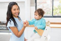 Happy brunette feeding her baby Stock Photography