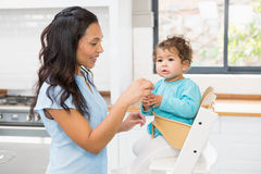 Happy brunette feeding her baby. In the kitchen Royalty Free Stock Photography